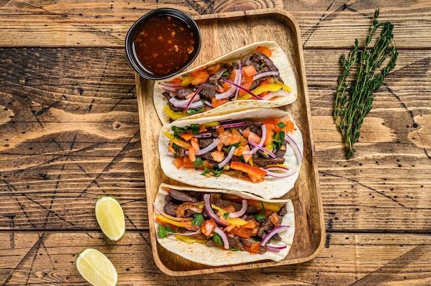 Taco's met rundvlees, ui, tomaat, paprika en salsa. mexicaans eten. houten tafel. bovenaanzicht.