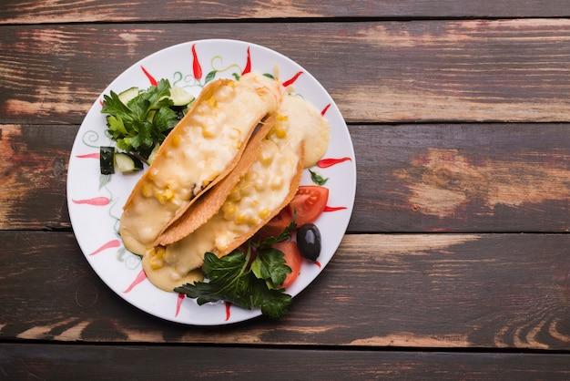 Taco's met saus onder groenten op schotel