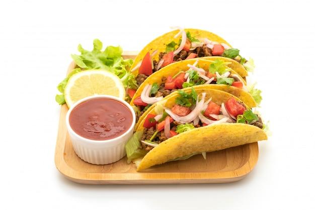 Taco's met vlees en groenten op wit wordt geïsoleerd