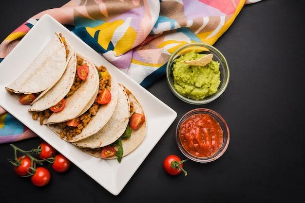 Taco's op plaat dichtbij servet en sausen