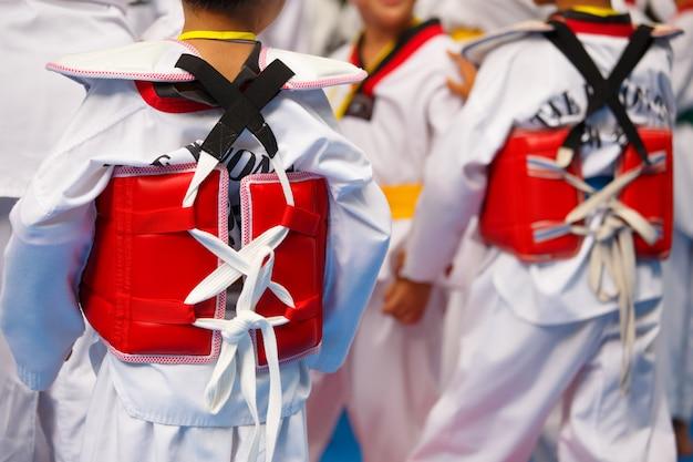 Taekwondo-atleten met uniform en rood pantser