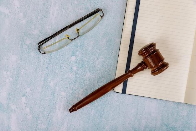 Tafel advocaten kantoorbenodigdheden rechter bureau met houten rechters voorzittershamer een notitieboekje en leesbril