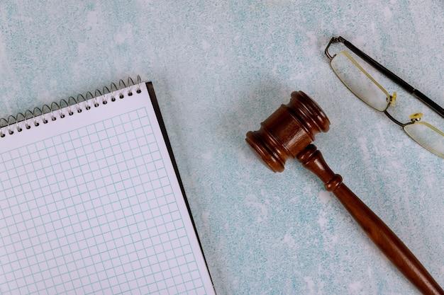 Tafel advocatenkantoor levert rechter bureau met houten rechters voorzittershamer een notitieboekje met leesbril