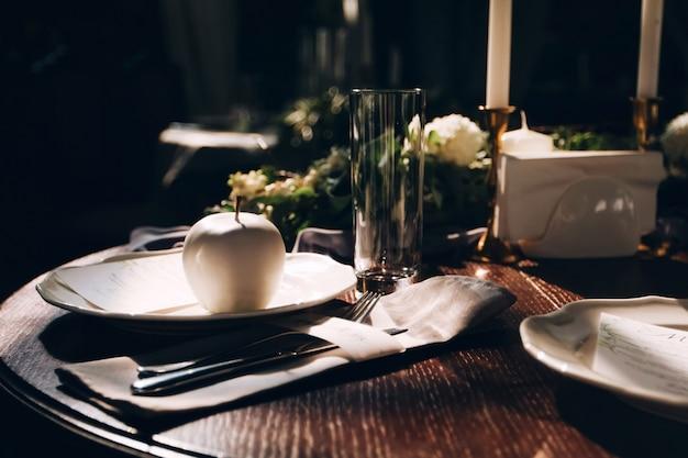 Tafel afspraken voor bruiloft. appel in witte chocolade. menukaart op een witte plaat. witte appel. gerechten op een houten tafel. geserveerd tafelblad uitzicht. rustieke bruiloft tafel