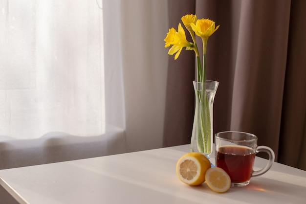 Tafel bij het raam met witte en bruine gordijnen is een kopje thee, citroen en gele narcissen in een glazen vaas.