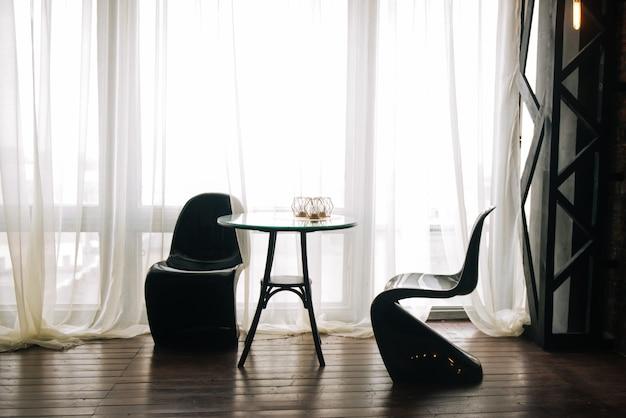 Tafel en ongebruikelijke zwarte stoelen staan op de achtergrond van het raam, keuken interieur, romantisch