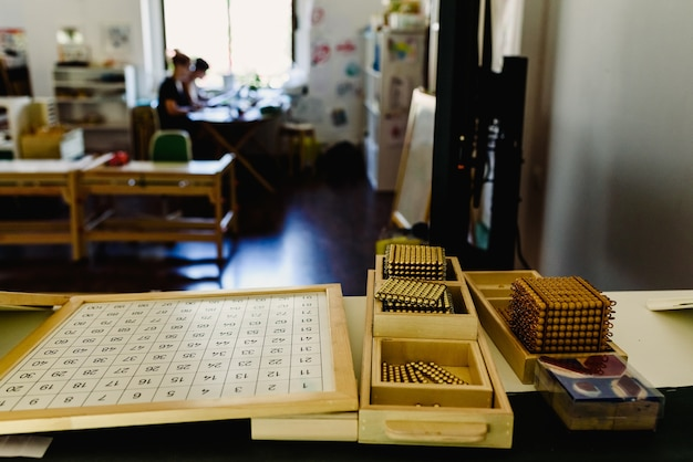 Tafel en rekken met montessori-materiaal, gekleurde items en houten cilinders