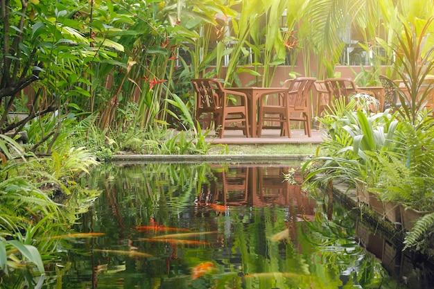 Tafel en stoelen in de tuin omgeven door prachtige bomen.