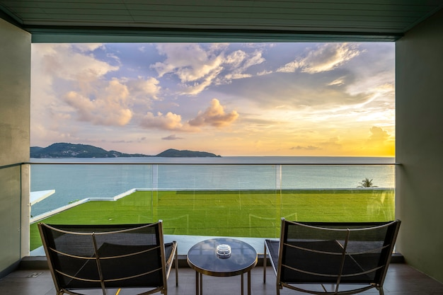 Tafel en stoelen op een balkon met uitzicht op zee, vlakbij de zee.