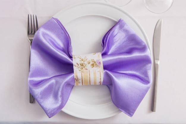 Tafel gelegd voor bruiloft, een romantisch diner of andere evenementen. bord versierd met een stoffen strik