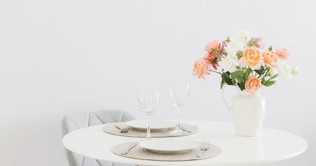 Tafel geserveerd met boeket rozen in scandinavische stijl