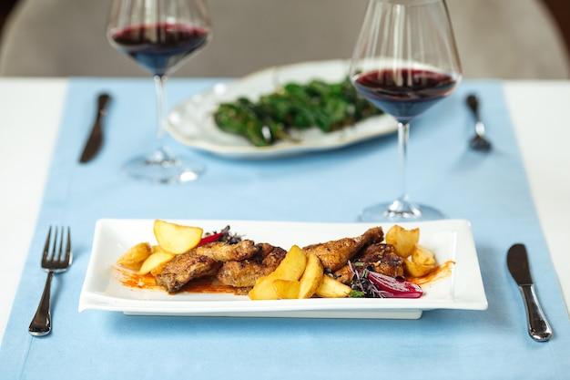 Tafel geserveerd met geroosterde kip met aardappelen en spaanse padron pepers met rode wijn