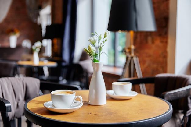 Tafel in café, twee witte kopjes koffie en vaas met boeket bloemen