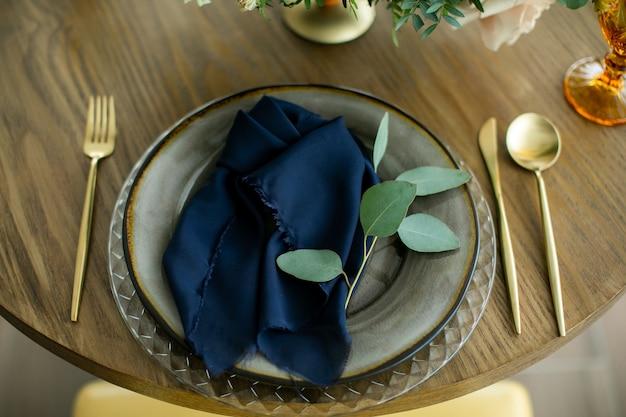 Tafel instelling, plaat, vork, mes, servetten en verse bloemen.