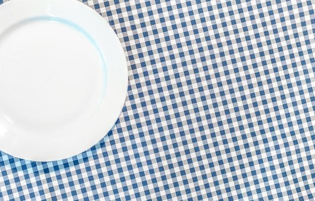 Tafel met blauwe picknickkleed en bord