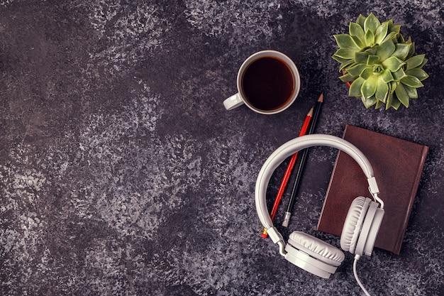 Tafel met blocnote, koptelefoon en koffie