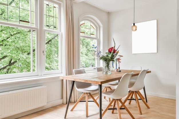 Tafel met bloemen en stoelen bij ramen en abstract schilderij in lichte eetkamer overdag