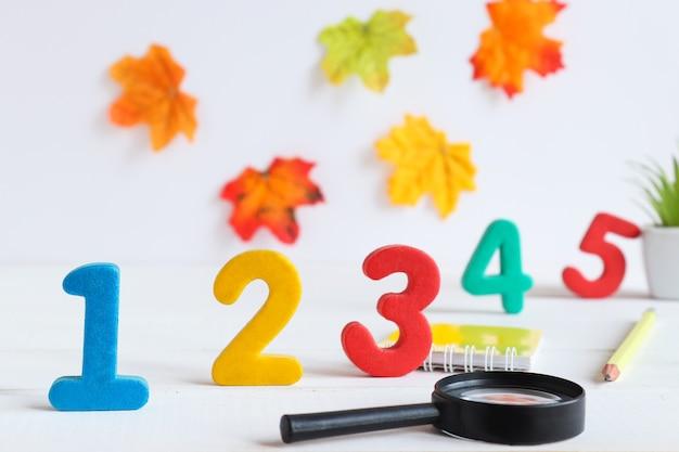 Tafel met cijfers en schoolspullen vergrootglas cijfers 15 notitieblok en pen