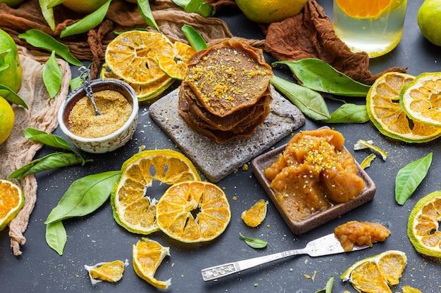 Tafel met droge citrusvruchten en rauwe pannenkoeken bij een kom vol mandarijnjam