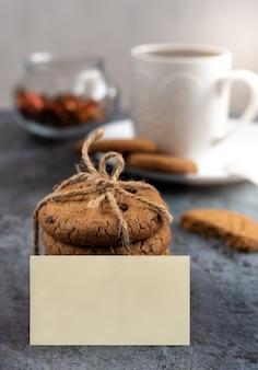 Tafel met een kopje koffie of thee en koekjes verlicht door ochtendlicht, blanco sticker voor inscriptie