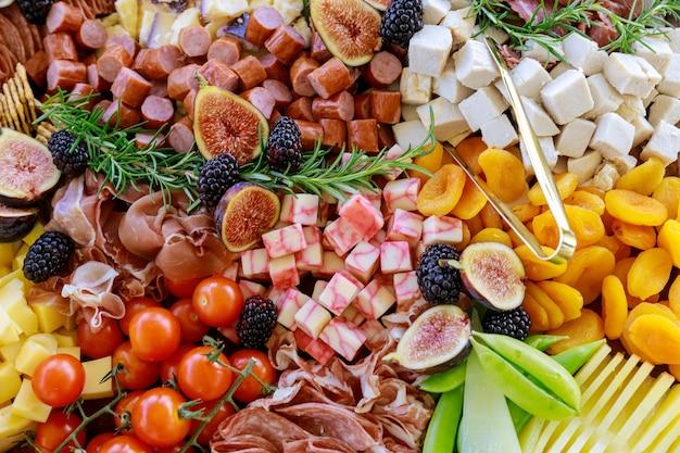 Tafel met een variëteit of assortiment van kaas, fruit en delicatessen. detailopname.