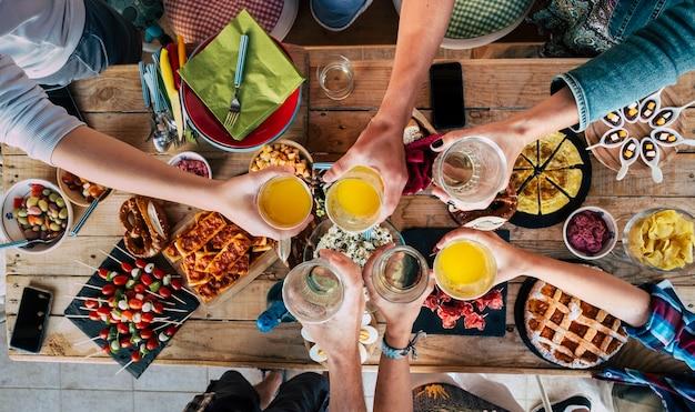 Tafel met eten en vrienden die samen klinken en proosten in vriendschap, plezier maken en vieren and