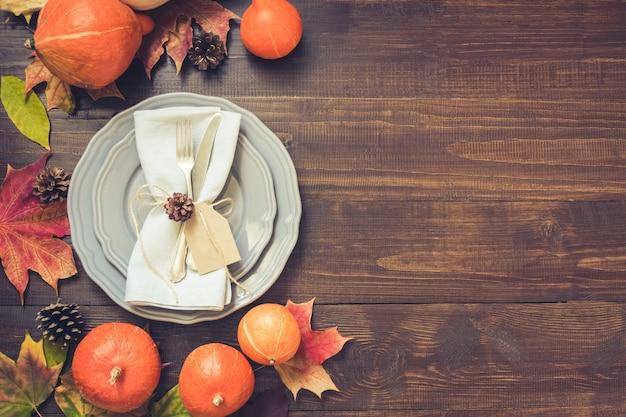 Tafel met gevallen bladeren, pompoenen, kruiden, grijs bord en bestek. bovenaanzicht,