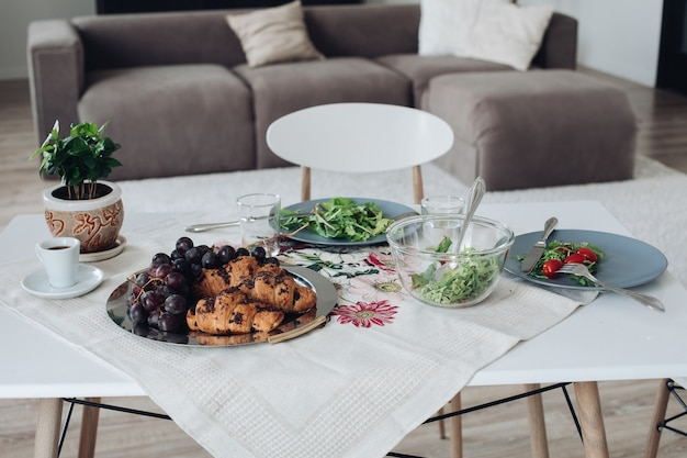Tafel met gezond lekker ontbijt omgeven door modern interieur op zomerochtend. smakelijk vers voedsel biologische tomaten groen croissant en fruit in gerechten op tafel afspraken