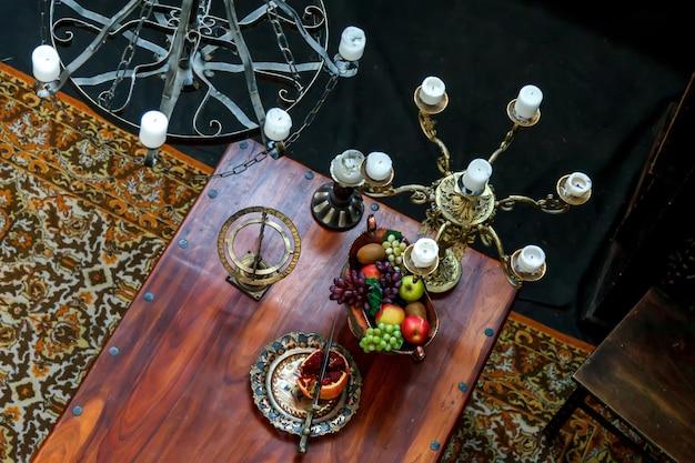 Tafel met groenten en fruit in middeleeuwse kamer met kroonluchters en kaarsen. uitzicht vanaf de bovenkant. stijl van oude feesten met zilveren schotels, fruit. auteursrecht ruimte. grote ruimte voor een inscriptie of logo