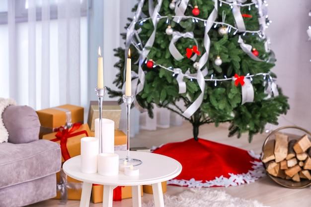 Tafel met kaarsen in de kamer versierd voor kerstmis