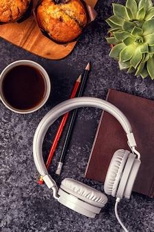 Tafel met kladblok, koptelefoon en koffie.