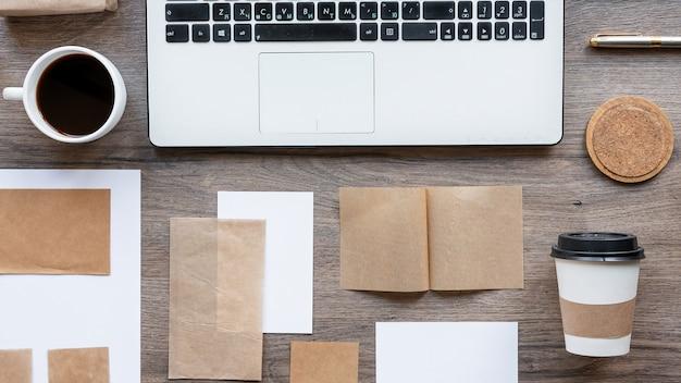 Tafel met lifestyle-dingen. laptop, twee kopjes koffie, decoratiepapier met houten tafel. bovenaanzicht