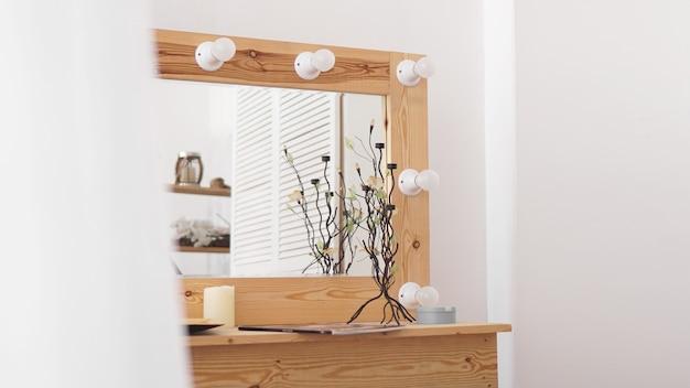 Tafel met make-upproducten en spiegel in de buurt van witte muur. interieur van de kleedkamer. modern interieur in de meisjesslaapkamer