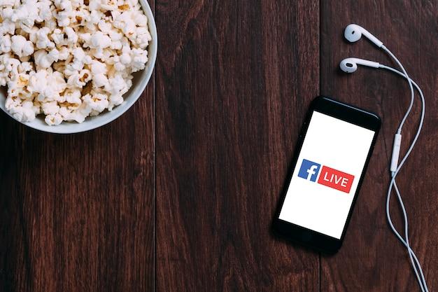 Tafel met popcorn fles en facebook live-logo op apple iphone en oortelefoon.