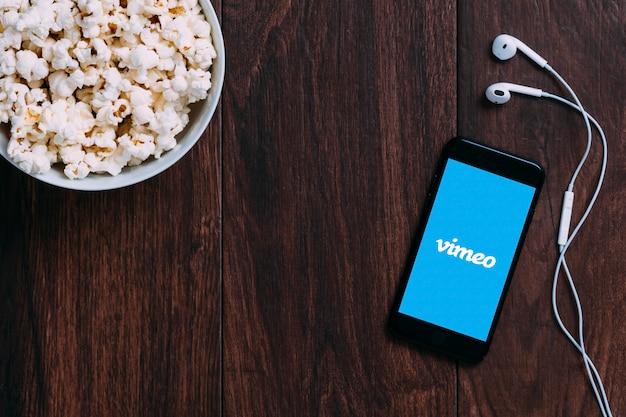 Tafel met popcorn fles en vimeo-logo op apple iphone en oortelefoon.