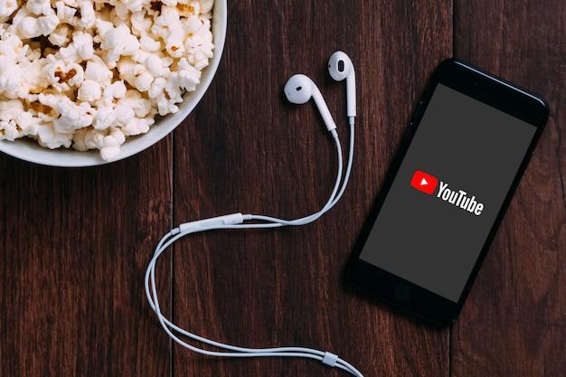 Tafel met popcorn fles en youtube-logo op apple iphone en oortelefoon.