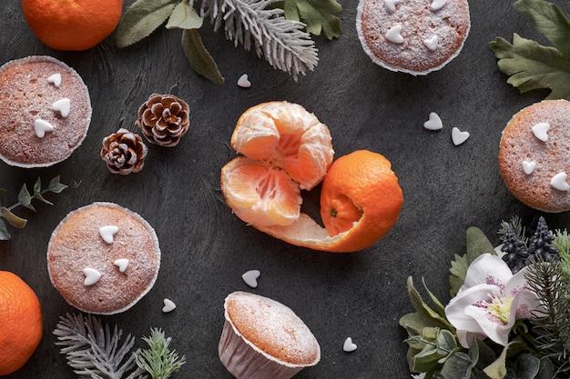 Tafel met satsuma's, met suiker bestrooide muffins en kerststerkoekjes op donker