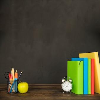 Tafel met schoolboeken wekker briefpapier en appel