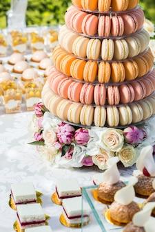 Tafel met snoep versierd met bloemen en macaron cake