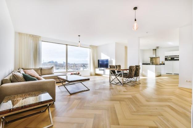 Tafel met stoelen en comfortabele bank in ruime woonkamer ontworpen in minimale stijl in appartement