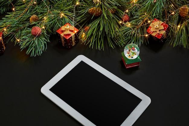Tafel met tabletcomputer, kerstspeelgoed, sterren en pluizige dennentakken. vrije ruimte voor tekst. bovenaanzicht. ruimte kopiëren. detailopname