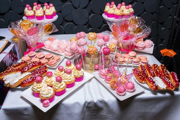 Tafel met verschillende zoetigheden en cupcakes op een kinderfeestje