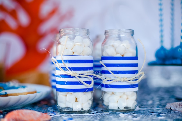 Tafel met zee decor en bord met snoep, snoepjes, koekjes en siert potten met marshmallow