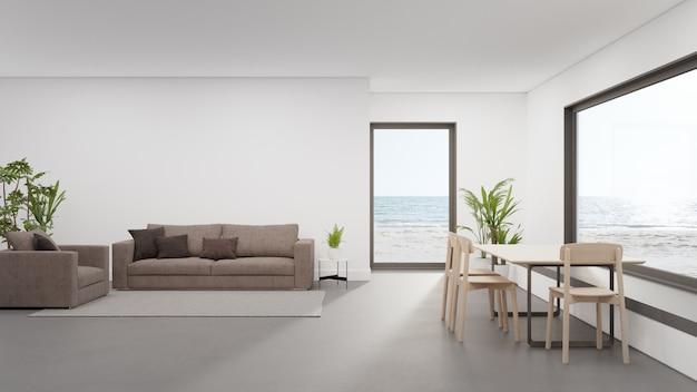 Tafel op betonnen vloer van grote eetkamer in de buurt van woonkamer en bank in moderne strandhuis of luxe hotel.