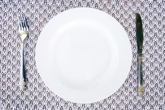 Tafel opstelling. wit porseleinen bord op een wit tafelkleed met een servet.