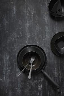 Tafel set geserveerd zwarte keramische pan, bord met vork en lepel en andere keukenapparatuur op dezelfde kleur stenen achtergrond, kopieer ruimte. bovenaanzicht.