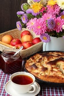 Tafel-stilleven met taart, rode appels, jam, thee in de beker en een boeket roze chrysanten