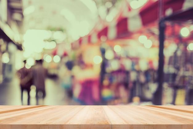Tafel, toonbank in winkel, achtergrond voor productweergavesjabloon, leeg houten bureau, plank, toonbank over onscherpte winkel met abstracte bokeh lichte achtergrond, houten tafelblad en vervaging winkel achtergrond.