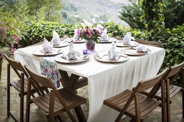 Tafel vol borden en een bloemenvaas op een mooi balkon met een prachtig uitzicht