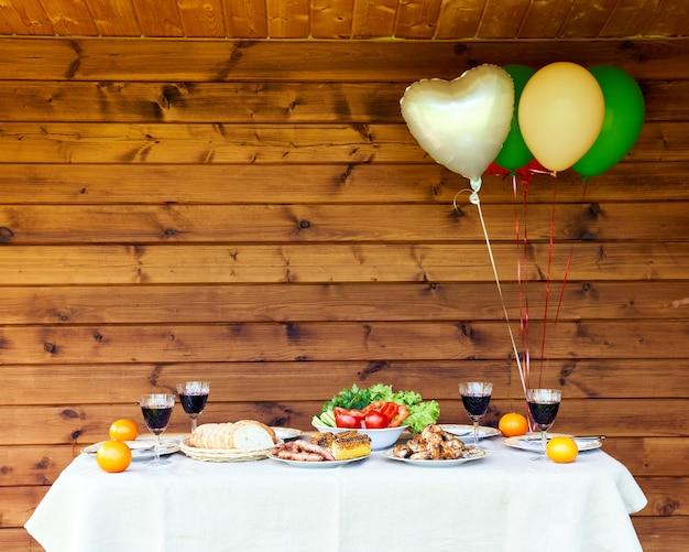 Tafel vol met groenten en vlees lucht ballonnen op houten